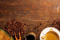 Kaffekopp och bönor på trätabellen royaltyfri foto