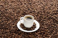 Kaffekopp och bönor som isoleras på vit bakgrund Arkivbild