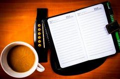 Kaffekopp och bok Arkivfoto