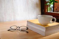 Kaffekopp och bok med exponeringsglas royaltyfri fotografi