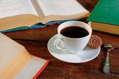 kaffekopp och bok på gammalt trä Arkivfoton