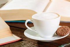 kaffekopp och bok på gammalt trä Royaltyfria Foton