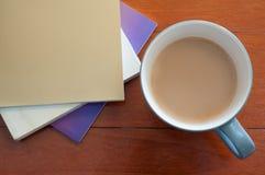 Kaffekopp och buntbok på röd wood modell Royaltyfria Foton