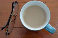 Kaffekopp och exponeringsglas på rött trä Fotografering för Bildbyråer