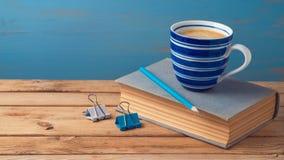Kaffekopp och gammal bok Arkivfoton