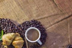 Kaffekopp och giffel på bönor och säcken Arkivbild