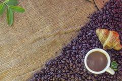 Kaffekopp och giffel på bönor och säcken Royaltyfri Fotografi