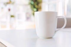 Kaffekopp och grå färgmidcenturyloveseat Royaltyfri Foto