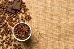 Kaffekopp och ingredienser på säckvävbakgrund arkivfoton