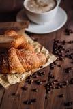 Kaffekopp och kaffebönor, giffel på den bruna trätabellen Royaltyfria Foton