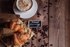 Kaffekopp och kaffebönor, giffel på den bruna trätabellen Arkivfoto