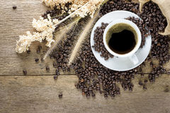 Kaffekopp och kaffebönor på den wood tabellen Arkivfoton