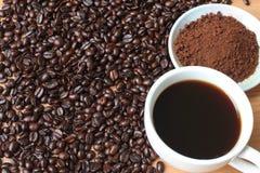 Kaffekopp och kaffebönor på trätabellen royaltyfri bild