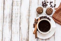 Kaffekopp och kaka på den vita trätabellen Arkivbild