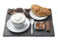 Kaffekopp och kaka på tabellen Latte- och cappuccinokonst med mjölkar kräm Varm kaffe och bulle med kanelbruna pinnar, kaffe Royaltyfri Foto