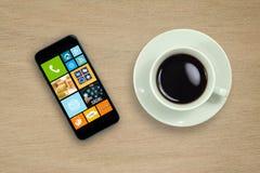 Kaffekopp och mobiltelefon på den wood tabellen Royaltyfria Foton