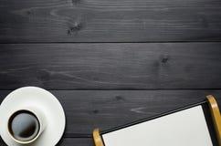 Kaffekopp och pappers- magasin på träbakgrund royaltyfria bilder