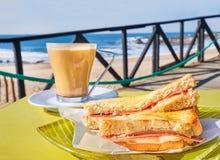 Kaffekopp och rostade bröd med ost och skinka på tabellen i kafét, terrass med havsvågsikt royaltyfri foto