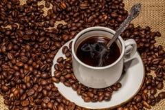 Kaffekopp och socker på ett tefat Arkivfoto