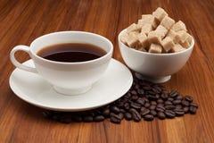 Kaffekopp och tefat på en trätabell Arkivbilder