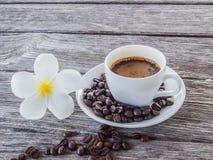 Kaffekopp och tefat på en trätabell Fotografering för Bildbyråer
