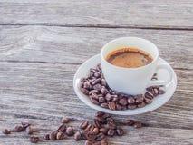 Kaffekopp och tefat på en trätabell Royaltyfria Foton