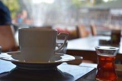 Kaffekopp och tefat på tabellen i coffee shop arkivbilder