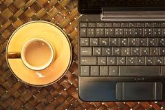 Kaffekopp på bärbara datorn Arkivbilder