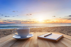kaffekopp på den wood tabellen på solnedgången eller soluppgångstranden Royaltyfri Foto