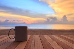 kaffekopp på den wood tabellen på solnedgången eller soluppgångstranden Arkivbild