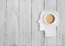 Kaffekopp på plattan i form för mänskligt huvud royaltyfri foto
