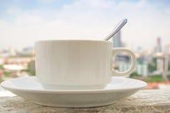 Kaffekopp som förläggas på byggnaden i morgonen Royaltyfri Bild