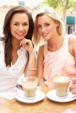 kaffekopp som tycker om två unga kvinnor royaltyfria foton