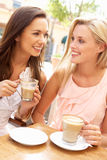 kaffekopp som tycker om två unga kvinnor arkivfoton