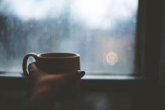 Kaffekopp som värme andan på en kall regnig dag Royaltyfri Foto