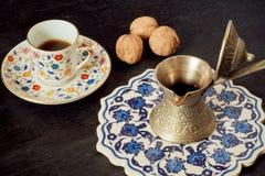 Kaffekopp, valnötter och turkisk stilcezve med den smakliga drinken på det blåa magasinet Royaltyfria Bilder