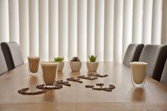 Kaffekoppar exponeringsglas och bönor Royaltyfria Foton