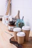 Kaffekoppar för tagande bort, olika format och kitchenware på trälunchräknare Fotografering för Bildbyråer