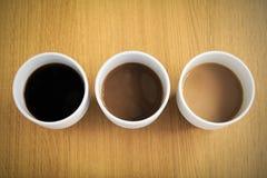 Kaffekoppar fyllde med kaffe med olika belopp av mjölkar royaltyfri bild