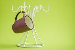 Kaffekoppar på en vit hängare Arkivfoto