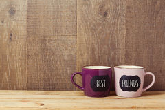 Kaffekoppar på trätabellen med svart tavlatecknet och bästa vän smsar Kamratskapdagberöm Royaltyfri Fotografi