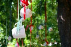 Kaffekoppar som hänger från en trädfilial på ett hipsterkafé Royaltyfri Foto