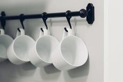 Kaffekoppar som hänger på krokar av kökväggen Arkivbild