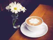 Kaffekoppen med den vita tusenskönan blommar garnering på trätabellen Arkivbilder