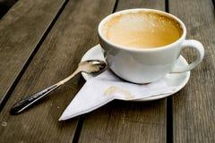 Kaffekoppen med kaffefläckar har inte tvättat koppen som förläggas på trätabellen Arkivfoto