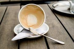 Kaffekoppen med kaffefläckar har inte tvättat koppen som förläggas på trätabellen Arkivfoton
