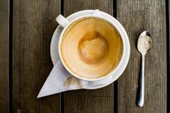 Kaffekoppen med kaffefläckar har inte tvättat koppen som förläggas på trätabellen Arkivbilder