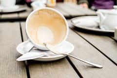 Kaffekoppen med kaffefläckar har inte tvättat koppen som förläggas på trätabellen Royaltyfria Bilder