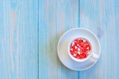 Kaffekoppen mycket av godisar sänker lägger på lantligt ljus - blå träbakgrund Arkivbild