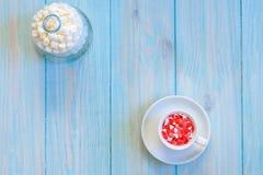 Kaffekoppen mycket av godisar sänker lägger på lantligt ljus - blå träbakgrund Royaltyfri Foto